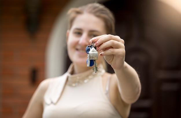 Zbliżenie młodej kobiety trzymającej klucz z nowego domu