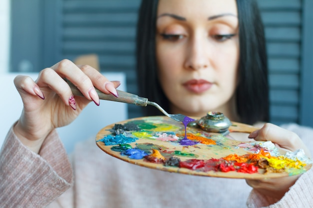 Zbliżenie młodej kobiety z czarnymi włosami miesza farbę na palecie z łopatką na białym płótnie
