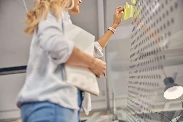 Zbliżenie młodej kobiety ze spiralnym szkicownikiem za pomocą samoprzylepnych papierowych notatek podczas pracy w nowoczesnym biurze