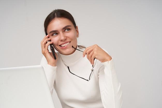 Zbliżenie młodej ładnej brunetki kobiety w białej dzianinowej poloneck uśmiechającej się wesoło, mając rozmowę telefoniczną i trzymając okulary, odizolowane na białej ścianie