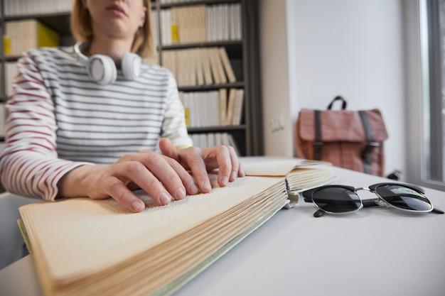 Zbliżenie młodej niewidomej kobiety czytającej książkę brajlowską w przestrzeni kopii biblioteki uczelni
