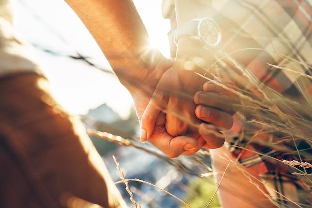 Zbliżenie młodej pary kochającej się w swobodnym ubraniu, trzymając się za ręce, stojąc na zewnątrz