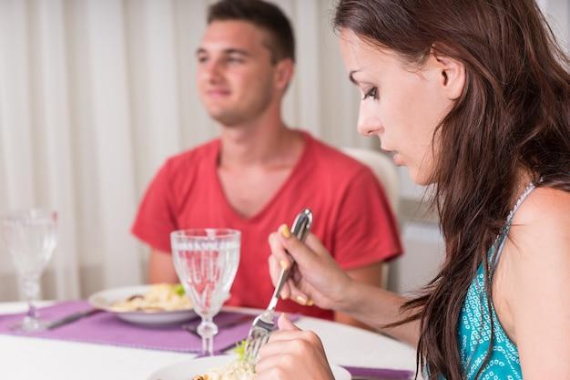 Zbliżenie młodej pary spożywającej kolację wraz z naciskiem na kobietę kręcącą makaron spaghetti na widelec przy stole