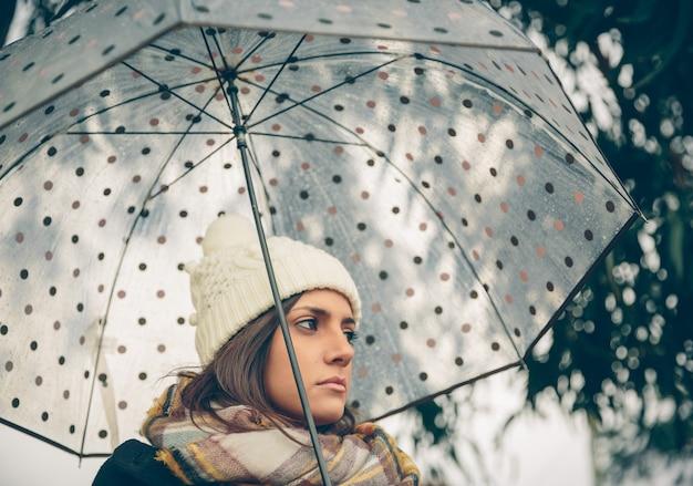 Zbliżenie młodej pięknej dziewczyny pod parasolem w jesienny deszczowy dzień