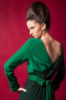 Zbliżenie młodej pięknej kaukaskiej brunetki w przepięknej zielonej sukience na czerwonym tle