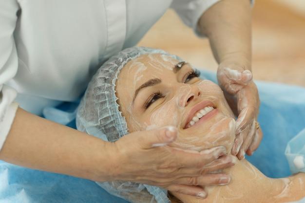 Zbliżenie Młodej Pięknej Kobiety Uśmiechającej Się Podczas Zabiegu Kosmetycznego - Specjalny Masaż Twarzy W Salonie Spa Premium Zdjęcia