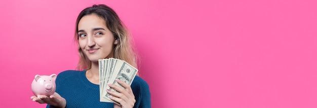 Zbliżenie młodej pięknej kobiety w niebieskim swetrze w okularach z pieniędzmi dolarów amerykańskich w ręku