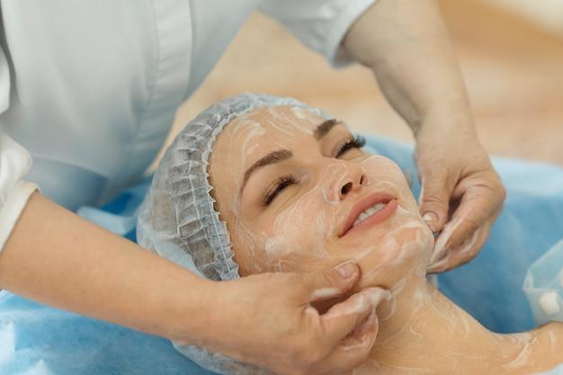 Zbliżenie młodej pięknej kobiety wykonuje specjalny masaż twarzy w salonie spa
