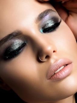 Zbliżenie młodej pięknej kobiety z doskonałej skóry i makijażu wieczorem