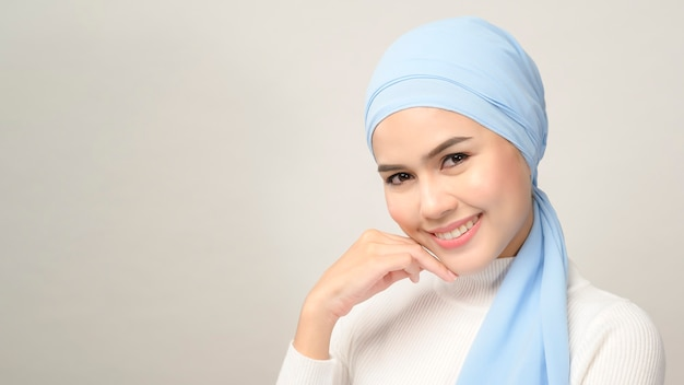 Zbliżenie młodej pięknej muzułmańskiej kobiety z hidżabu na białym tle studio, koncepcja pielęgnacji skóry muzułmańskiej urody.