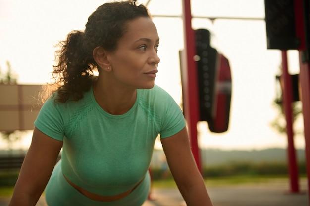 Zbliżenie młodej rasy mieszanej, african american piękna zdeterminowana kobieta sportowiec ćwiczy na świeżym powietrzu, robi pompki na boisku w lecie. zdrowy, aktywny styl życia i koncepcja fitness