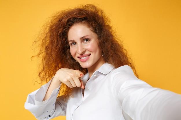 Zbliżenie młodej rudej kobiety dziewczyny w białej koszuli pozowanie na żółto pomarańczowej ścianie
