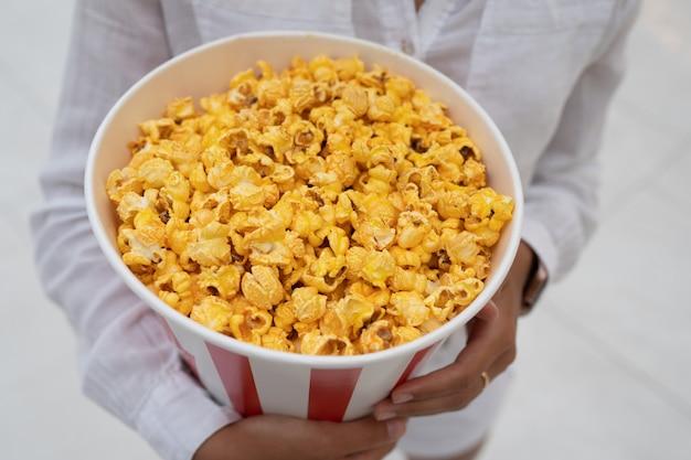 Zbliżenie młodej słodkiej dziewczyny trzymającej w rękach tubkę popcornu.