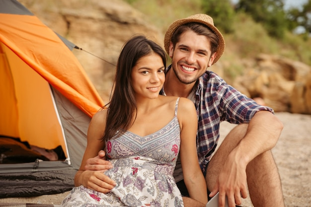 Zbliżenie młodej szczęśliwej pięknej pary siedzącej w namiocie na plaży