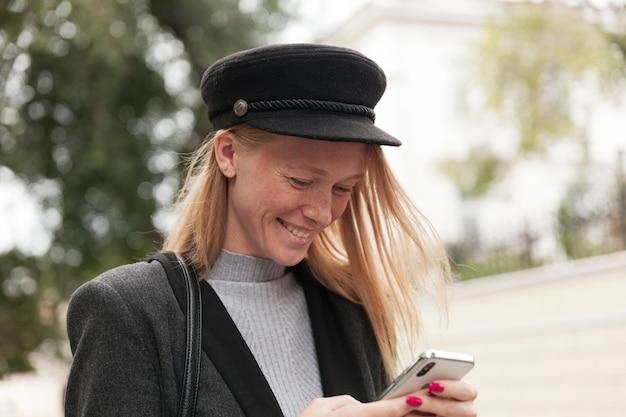 Zbliżenie młodej wesołej ładnej blondynki z przypadkową fryzurą, szczęśliwie patrząc na ekran swojego telefonu i uśmiechając się szeroko podczas rozmowy z przyjaciółmi