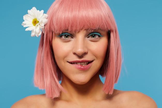 Zbliżenie młodej zielonookiej zalotnej kobiety z krótkimi różowymi włosami gryzącymi dolną wargę, patrząc ospale, ubrana w biały romantyczny kwiat we włosach