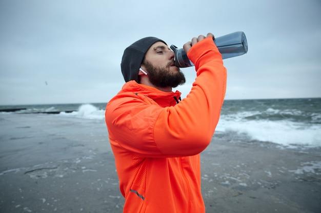 Zbliżenie: młody atrakcyjny ciemnowłosy brodaty biegacz ubrany w ciepłe sportowe ubrania, trzymając butelkę fitness w uniesionej ręce podczas picia wody po porannym treningu