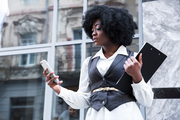 Zbliżenie: młody bizneswoman afryki gospodarstwa schowka przy użyciu telefonu komórkowego