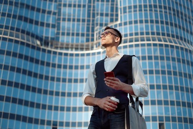 Zbliżenie. młody człowiek czytanie wiadomości na swoim smartfonie. zdjęcie z kopią - spacja.