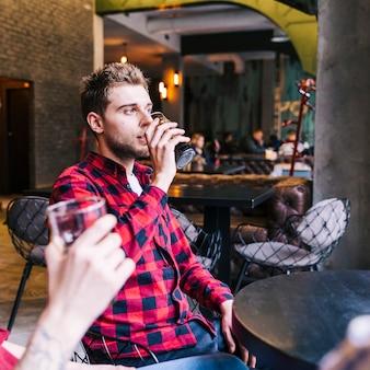 Zbliżenie: młody człowiek pije piwo ze swoim przyjacielem w pubie