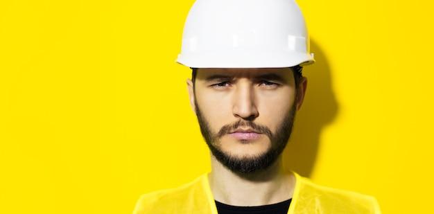 Zbliżenie młody człowiek poważny architekt, inżynier konstruktor, ubrany w biały kask ochronny i żółtą kurtkę na białym tle na żółtej ścianie.