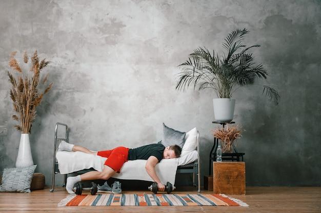 Zbliżenie: młody człowiek w mundurze sportowym odpoczywa, śpi na łóżku z hantlami. sportowiec odpoczywa i odkłada trening