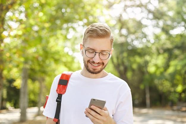 Zbliżenie: młody ładny facet z brodą, w słuchawkach i okularach, patrząc na swój telefon, będąc szczęśliwym i radosnym, stojąc nad parkiem w słoneczny dzień