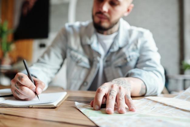 Zbliżenie: młody mężczyzna siedzi przy stole i zapisuje miejsca do odwiedzenia podczas przeglądania papierowej mapy