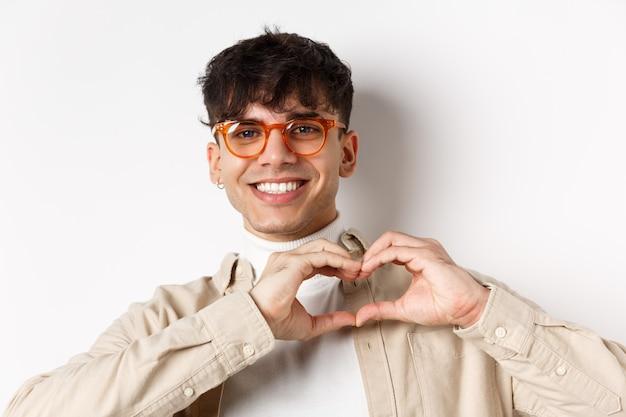 Zbliżenie: młody naturalny facet w okularach, uśmiechając się, pokazując gest serca kocham cię, stojąc na białej ścianie.