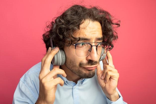 Zbliżenie: młody przystojny kaukaski mężczyzna w okularach i słuchawkach, patrząc na bok, słuchając muzyki na białym tle na szkarłatnej ścianie