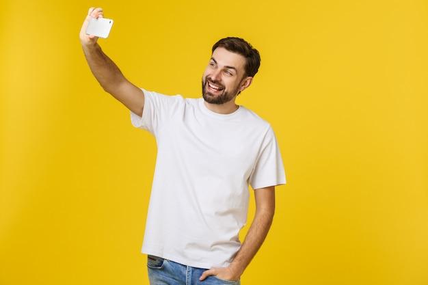 Zbliżenie młody przystojny mężczyzna patrzeje smartphone i bierze selfie. izolować.