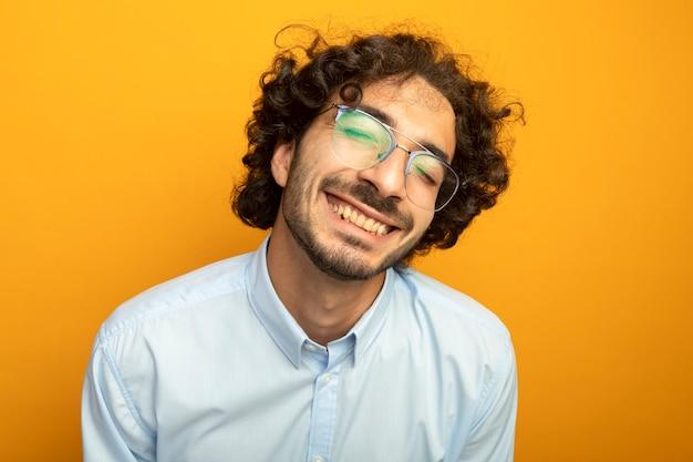 Zbliżenie: młody przystojny mężczyzna w okularach, patrząc z przodu na białym tle na pomarańczowej ścianie