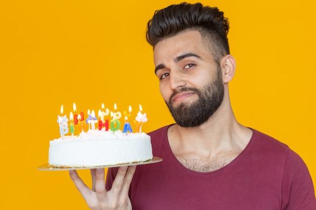 Zbliżenie młody przystojny mężczyzna zdmuchuje świeczkę z płonącego ciasta pozuje na żółtym tle
