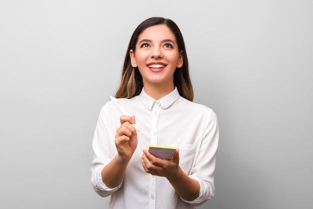 Zbliżenie młody rozochocony bizneswoman z pięknym zdrowym uśmiechu mienia piórem robi nowym pomysł notatkom i ciekawie przyglądającym up przeciw szarości ścianie