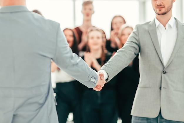 Zbliżenie młodych ludzi pewnie ściskających ręce