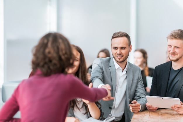 Zbliżenie młodych ludzi podających sobie ręce na spotkaniu w biurze