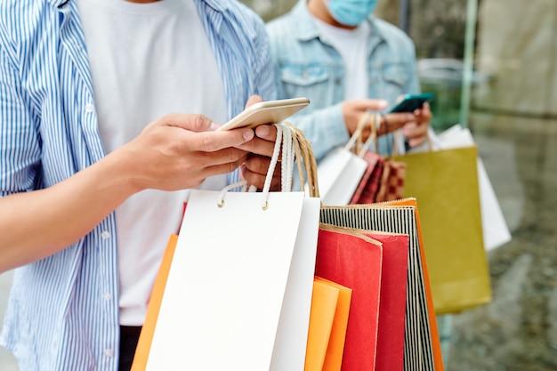 Zbliżenie młodych ludzi z torbami na zakupy, sprawdzających wyprzedaże i oferty za pośrednictwem aplikacji mobilnych