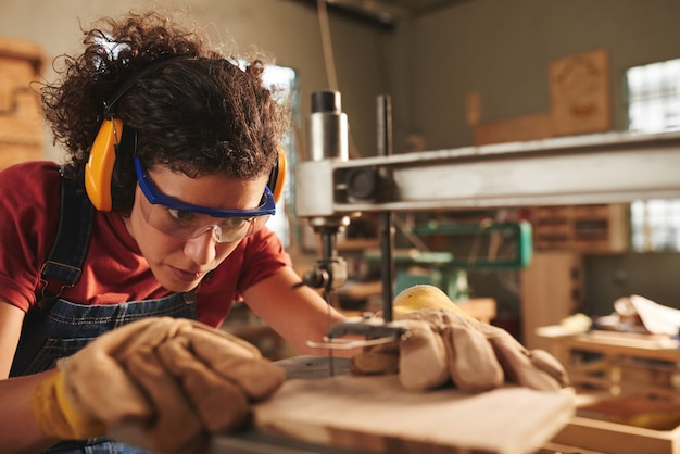 Zbliżenie młodych skoncentrowanych stolarz kobiet w okularach ochronnych i nauszników wiercenie otworu w drewnianej desce z wiertarką