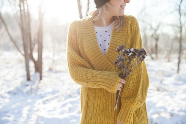 Zbliżenie młodych womans ręce trzymając suche kwiaty na słonecznym tle parku zimowego