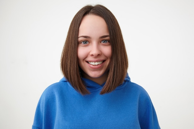 Zbliżenie młodych zadowolony piękny krótkie włosy brunetka kobieta bez makijażu, patrząc radośnie z przodu z szerokim uśmiechem, podczas gdy pozowanie na białej ścianie
