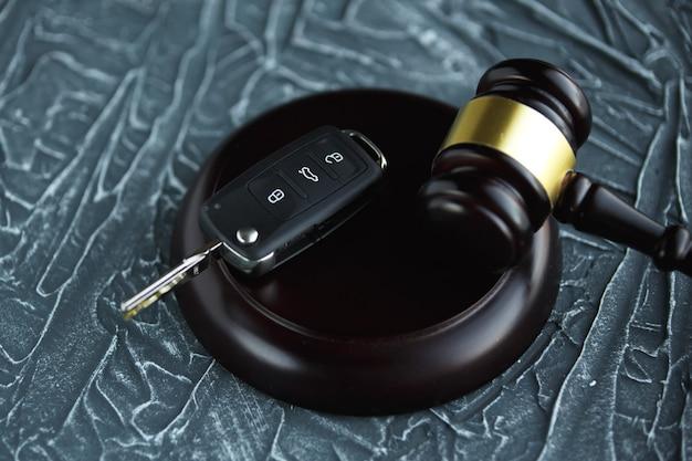 Zbliżenie młoteczka i kluczyka samochodowego na bloku dźwiękowym na tle szarości