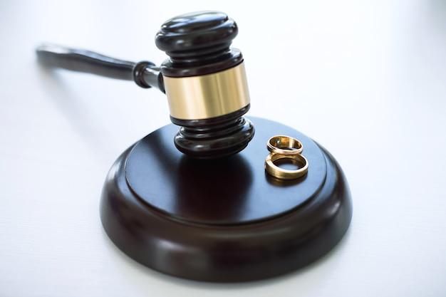 Zbliżenie młotek sędziego decydowanie o rozwodzie małżeństwa i dwa złote małżeństwo pierścień