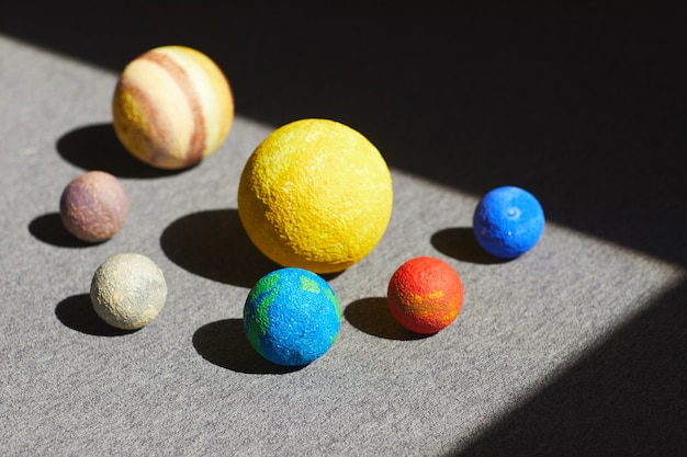 Zbliżenie modeli parady planet wokół słońca umieszczonego na oświetlonej podłodze, koncepcja astronomii