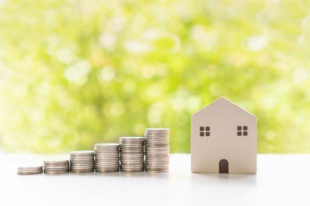 Zbliżenie modelu domu i pieniędzy na białym stole na zielonym tle bokeh. zbieraj pieniądze, wydatki domowe, konto, oszczędności i koncepcję inwestycji. leżał na płasko
