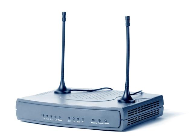 Zbliżenie: modem internetowy i odbiornik telewizyjny kanałów telewizyjnych z anteną stoi na białym stole na białej ścianie. koncepcja urządzenia umożliwiającego dostęp do internetu. przestrzeń reklamowa