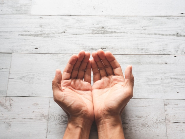 Zbliżenie modląc się ręce i światło słoneczne cień przyrody na widok z góry stołu z drewna