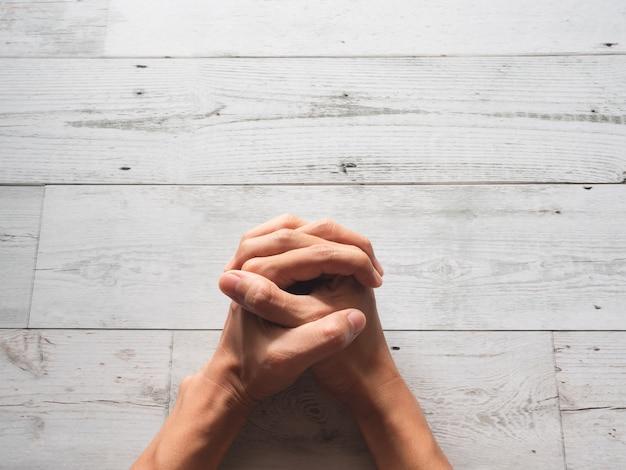 Zbliżenie modląc się ręce pięść i światło słoneczne natura cień na widok z góry stołu z drewna
