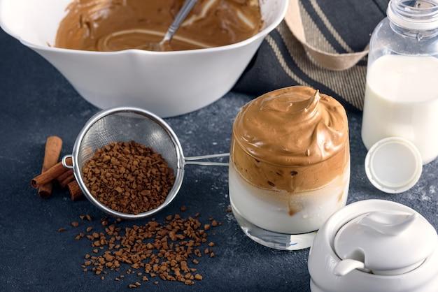 Zbliżenie modna kawa dalgona, proces tworzenia na szarym stole w kuchni