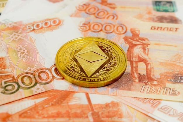 Zbliżenie monet ethereum na banknocie 5000 rubli rosyjskich. kryptowaluta etc.