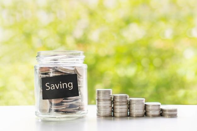 Zbliżenie monet w szklanym słoju i na białym stole na zielonym tle bokeh. zbieraj pieniądze na przyszłość, koncepcję oszczędności i inwestycji. leżał na płasko